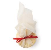 Handflächengroßes, halbrundes Ölbad verpackt in ein Musselintuch, zusammengebunden mit einem roten Band