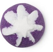 Ein halbrundes, violettes Zuckerpeeling mit einer weißen Dekoration aus weißem Meersalzpeeling an der Oberseite