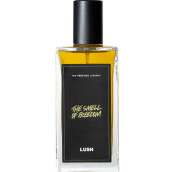 A bottle of The Smell of Freedom Lush perfume. The perfume is dark yellow in colour and contained in a rectangle bottle featuring a black lid and label.