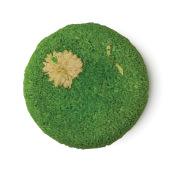 Karma Komba ist ein grünes, festes Shampoo ohne Verpackung mit einer getrockneten Kamillenblüte als Dekoration