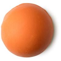 Diese Gelb-orange Badebombe duftet erfrischen nach Zitrus und Kräutern