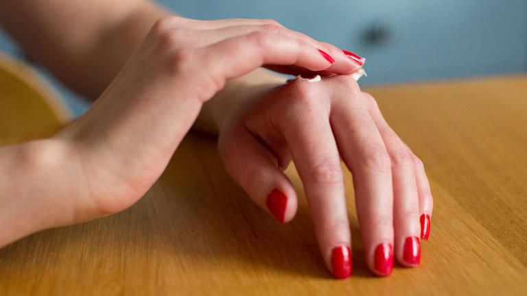 Zwei Frauenhände mit rotem Nagellack tupfen sich eine geschmeidige Handcreme auf den Handrücken auf.