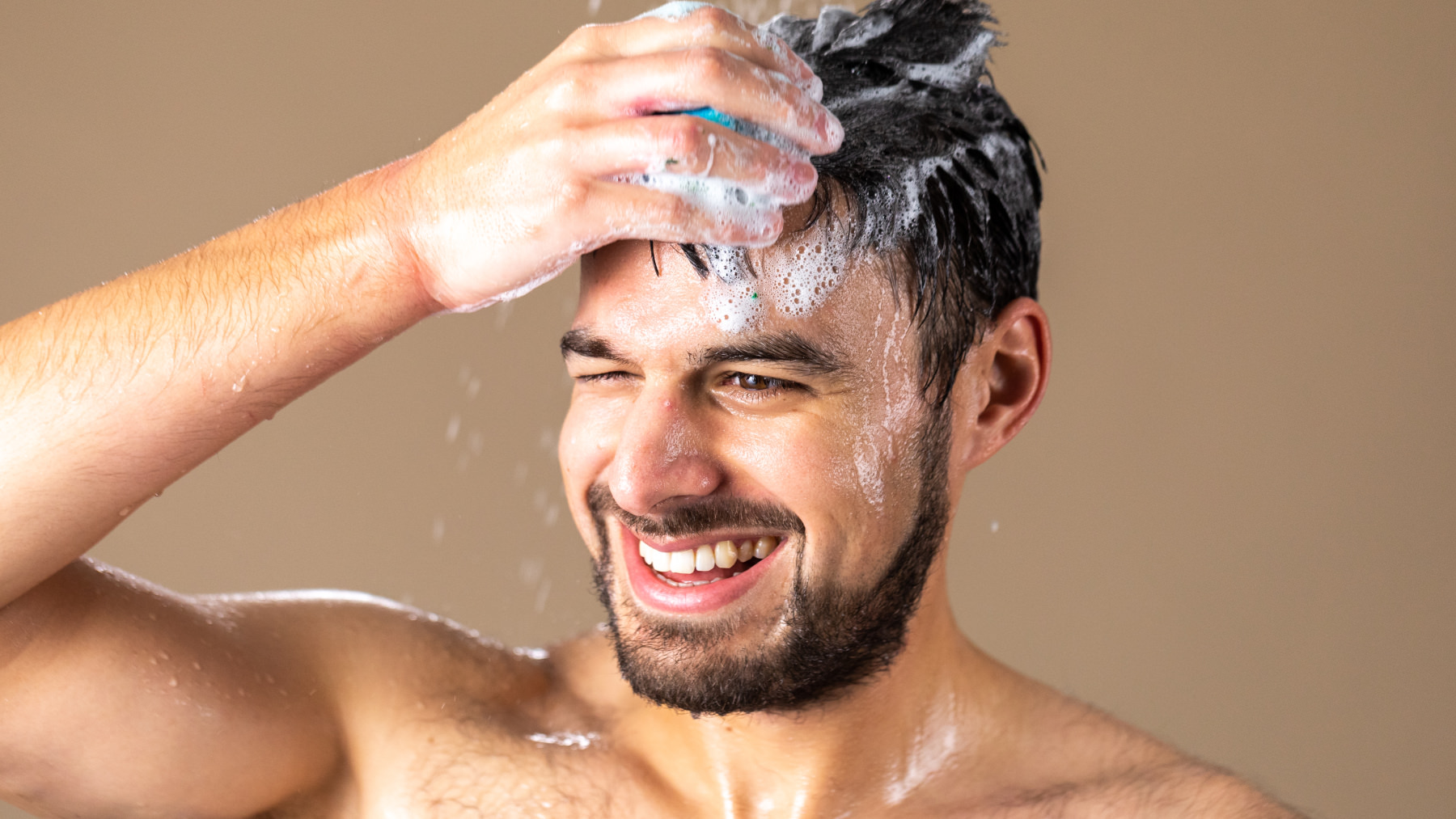 A man shampooing his dark hair
