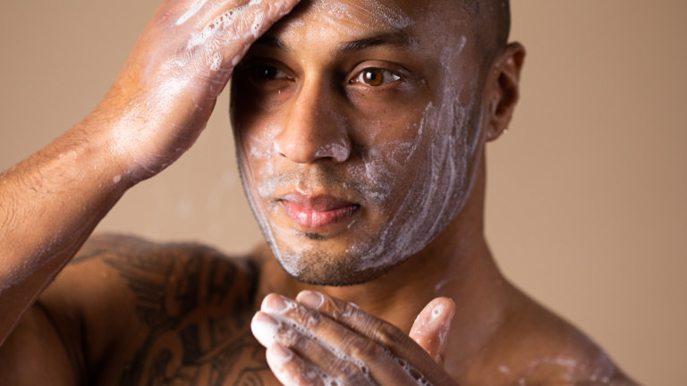 A man with shaved head washing his face