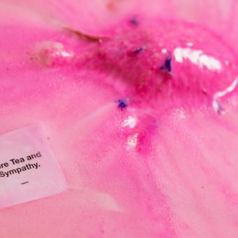 Pinke Badebombe in Form eines Teekessels löst sich sprudelnd im Wasser auf