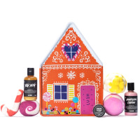 Gingerbread house shaped present with bath bombs, bubble bars, shower gels and a lip scrub surrounding it on a white background