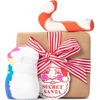 Un regalo de navidad con envoltorio navideño compuesto por un papel marrón y un lazo rojo y blanco con productos al lado