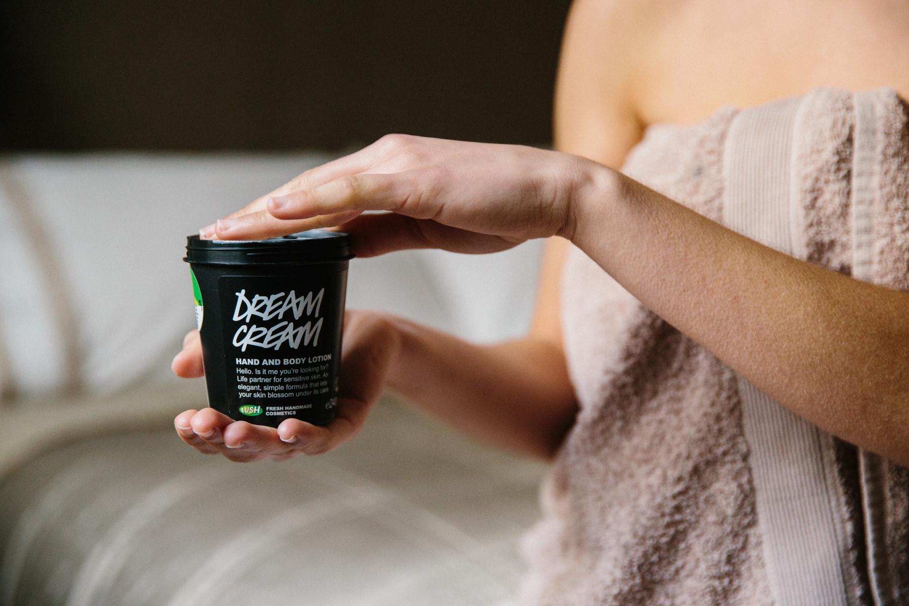 Žena drží kelímek tělového krému Dream Cream