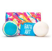 caja de regalo con envoltorio de colores rosa, azul, amarillo y naranja con dos bombas de baño como contenido