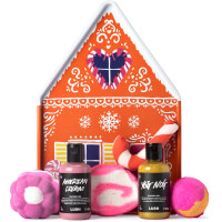 gingerbread house shaped tin with products around it