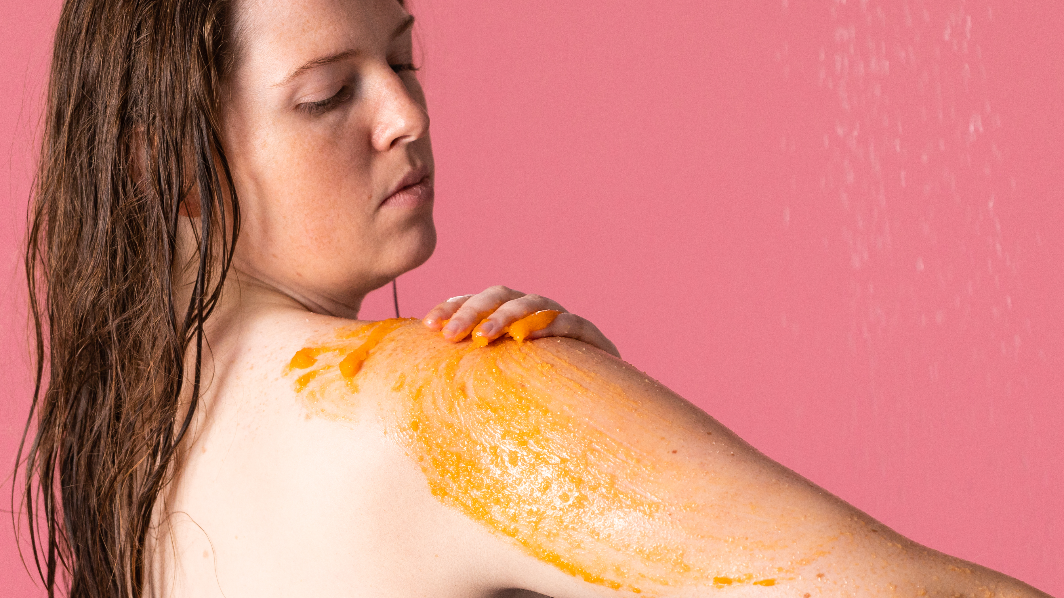 a lady in the shower using orange scrub on pink background