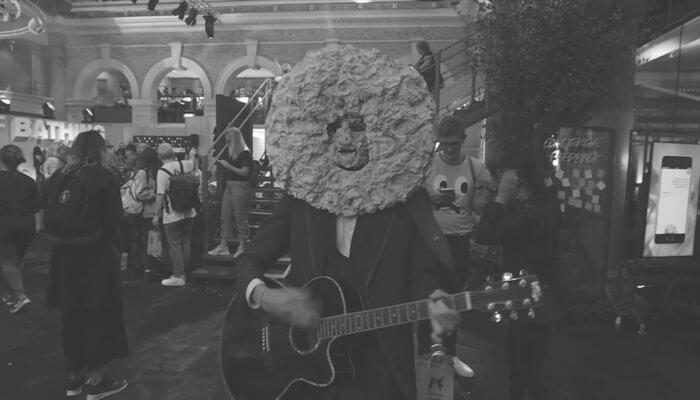 Man playing guitar wearing mask