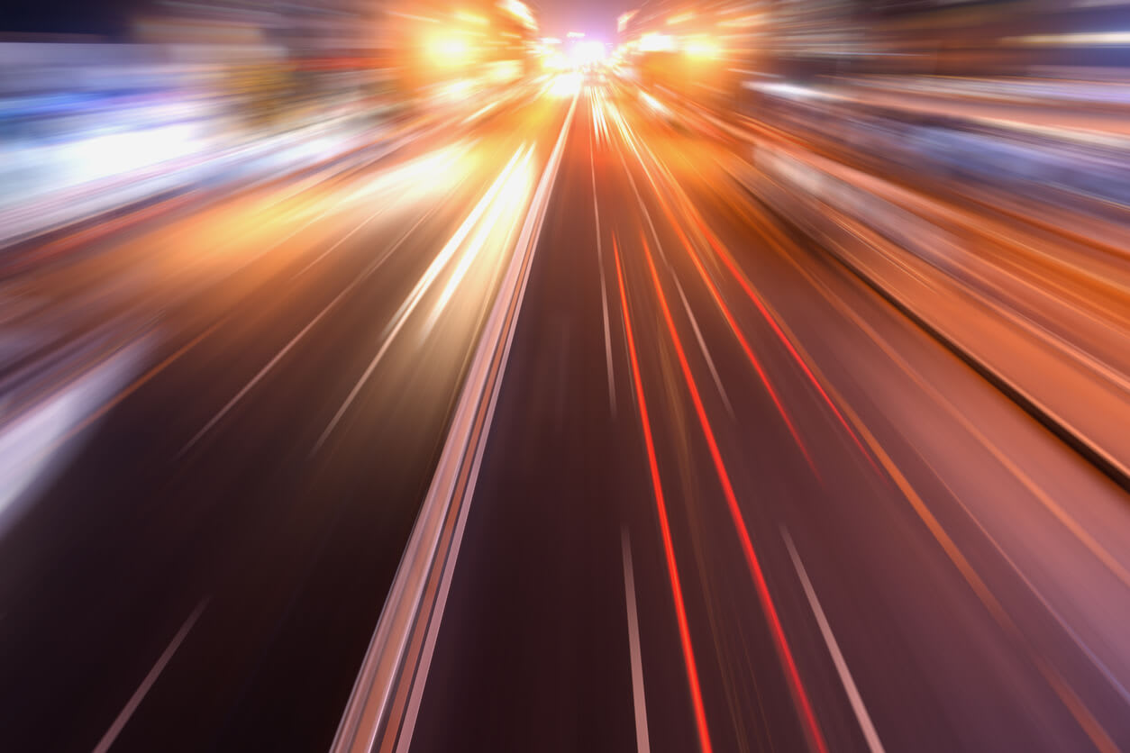 Picture of a car heading down a highway at blurred speeds.