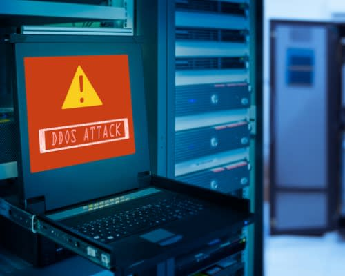 Red screen on a laptop in a server room with alert that reads DDoS ATTACK.