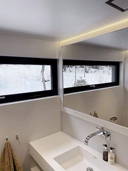 Bad med LED-striper langs tak over speil