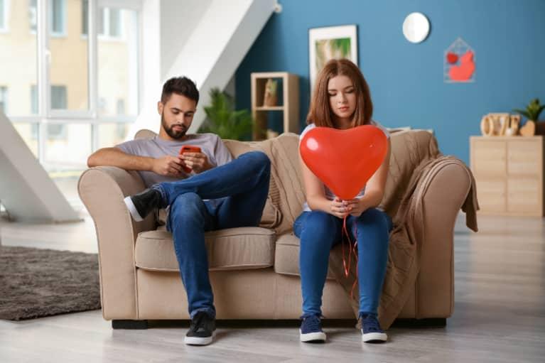 Hombre mirando su teléfono mientras su pareja sostiene un globo en forma de corazón