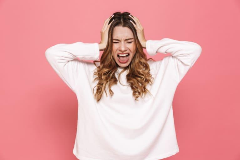 Mujer gritando mientras se tapa los oídos