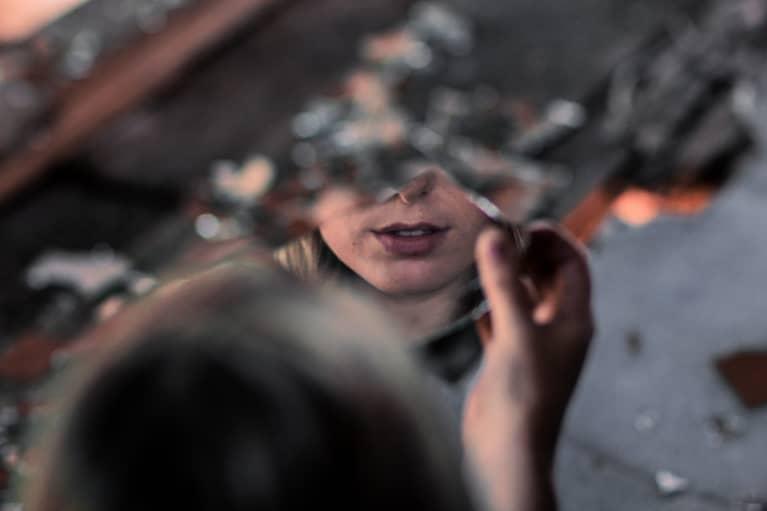 Persona mirándose en un espejo roto