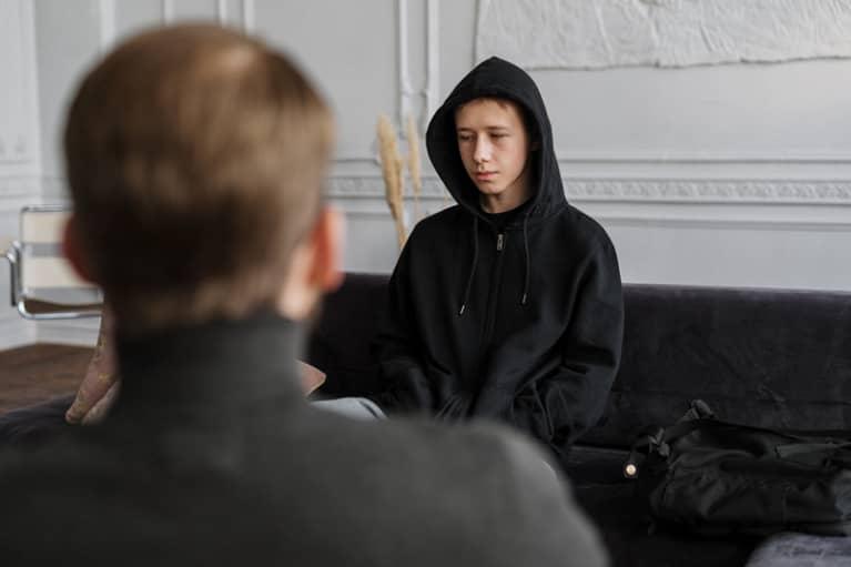Psicólogo atendiendo a joven en terapia
