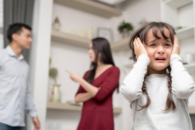 Pareja discutiendo mientras niña llora