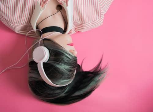 ピンクの床に寝転びながらヘッドフォンをする女性