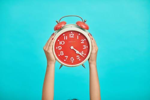 青い背景に掲げられた赤い時計