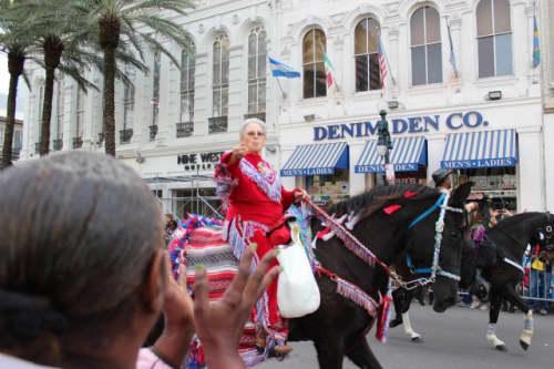 馬に乗ってネックレスを投げる男性