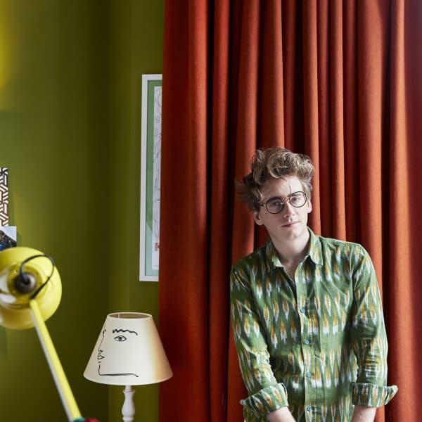 customer portrait in front of orange curtain