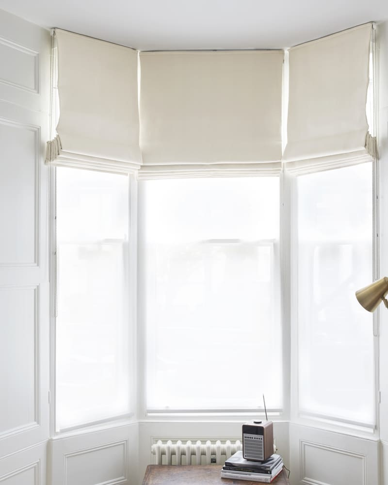 White bay windows and white roman blinds