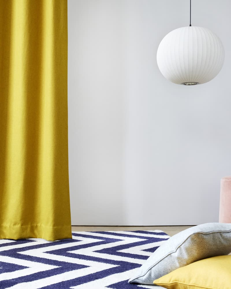 Bright yellow curtains and cushions on a stripped rug