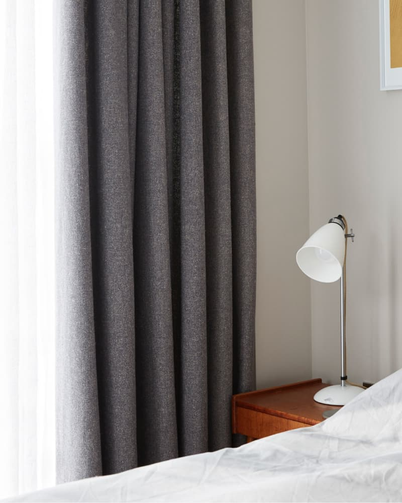 bedside table beside grey curtains
