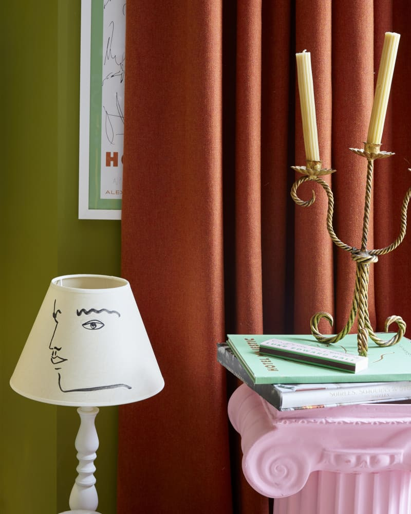 orange curtain behind pink pillar and lamp