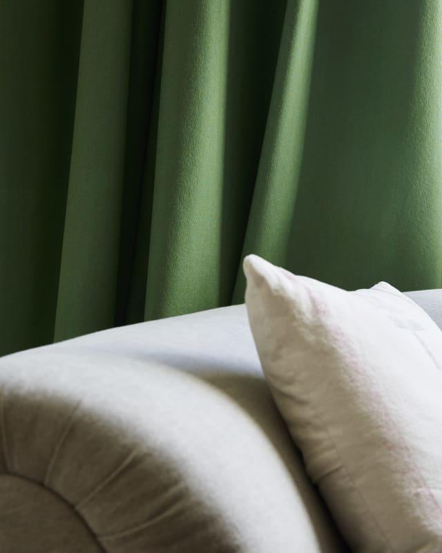 Green curtain behind white sofa