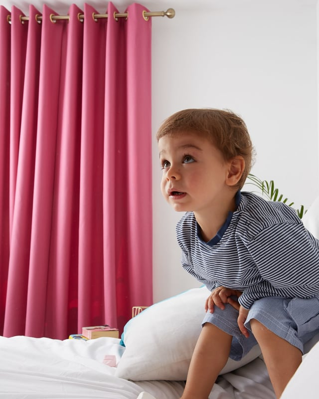 Child in front of Pink wool curtain