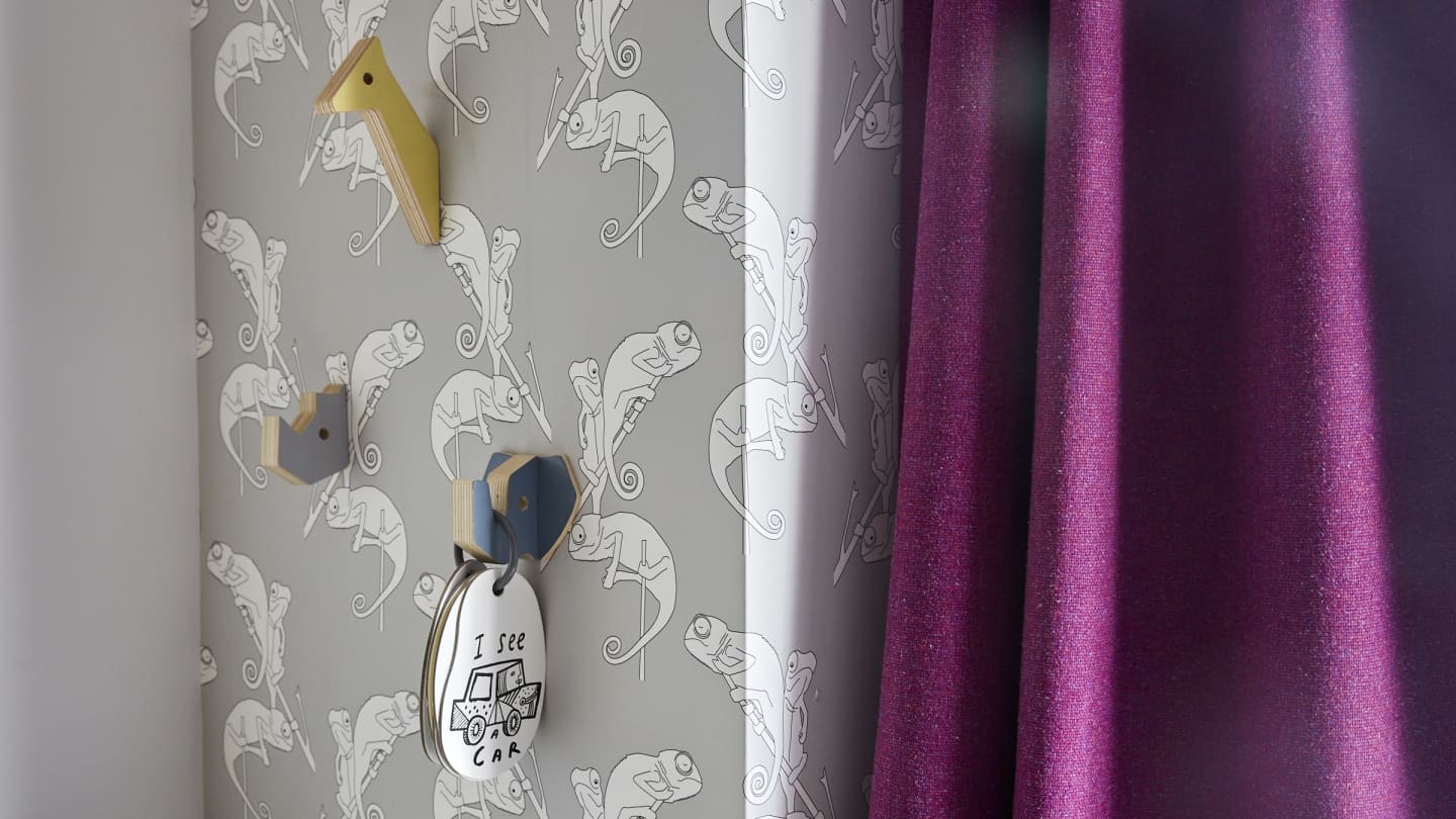 Chameleon wallpaper and pink curtain close up