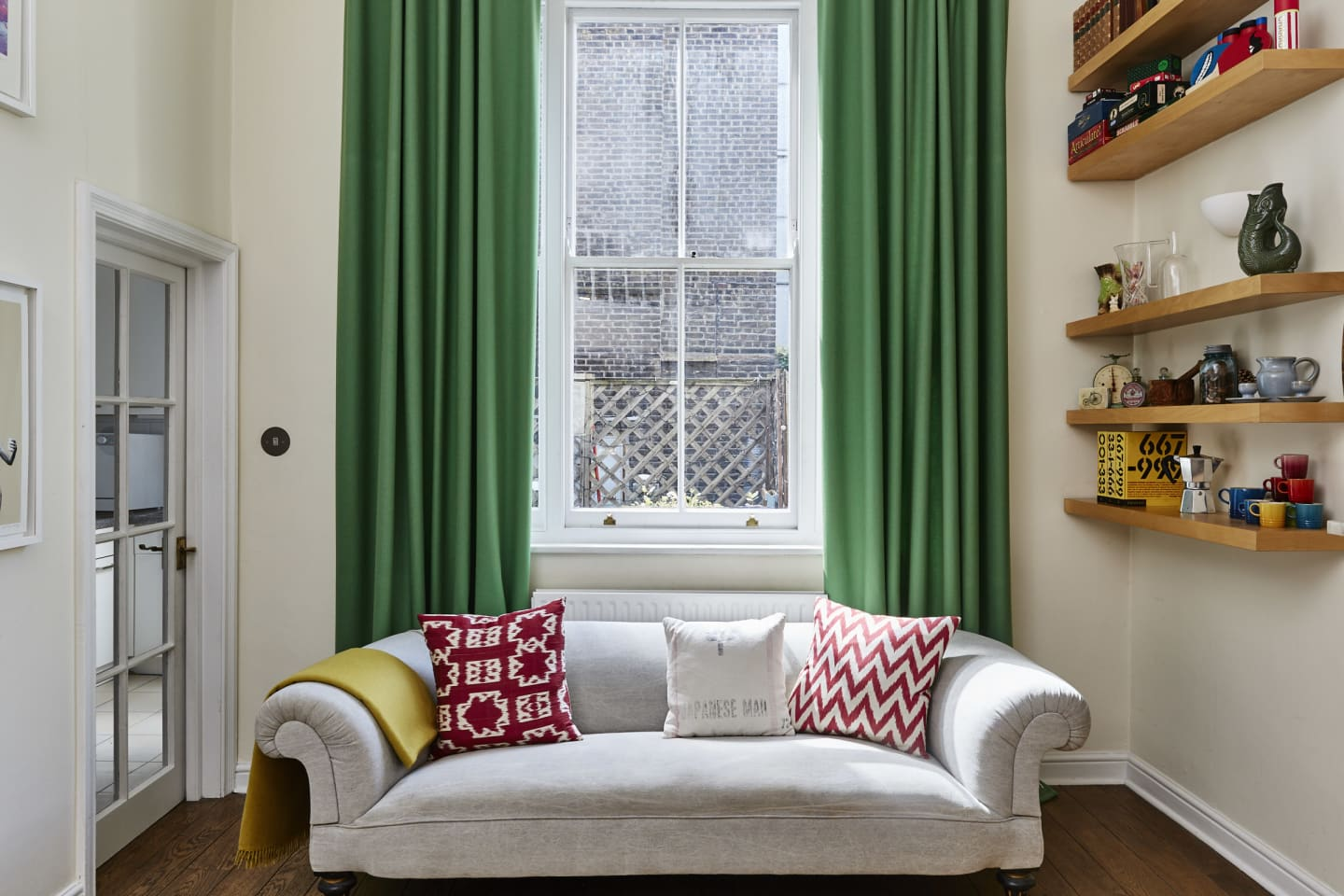 Living room with grey sofa and green woollen curtains