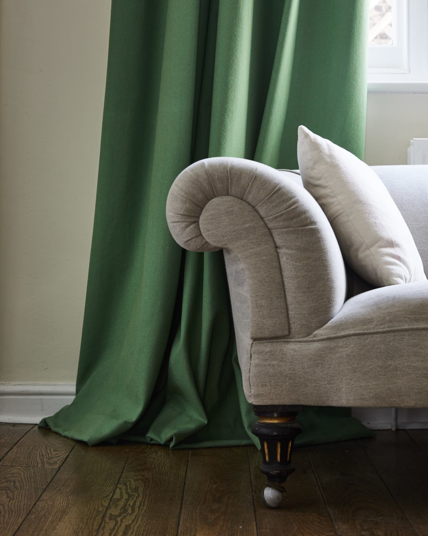 Corner of sofa and bottom of green wool curtains