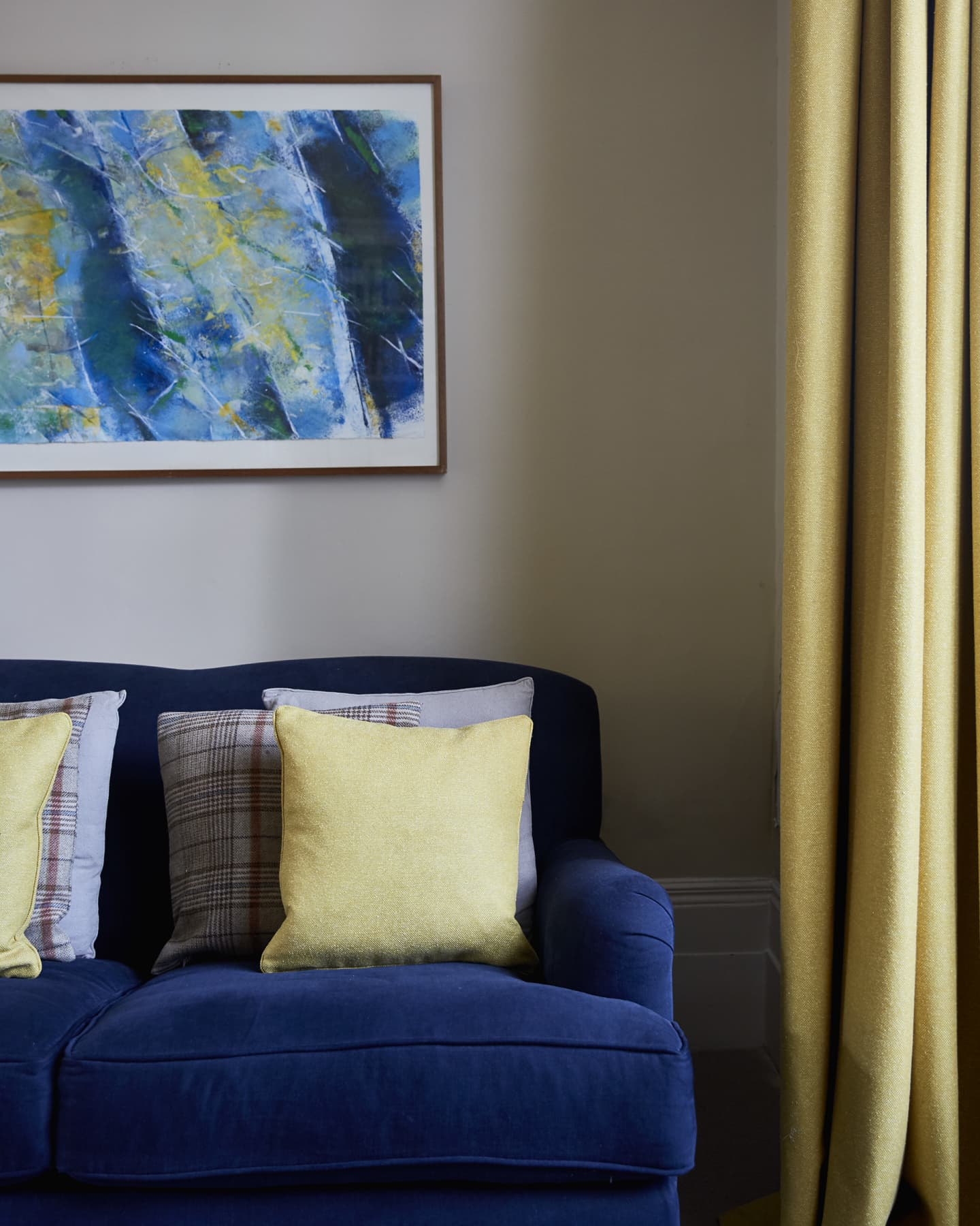 Navy sofa paired with yellow cushions and curtains