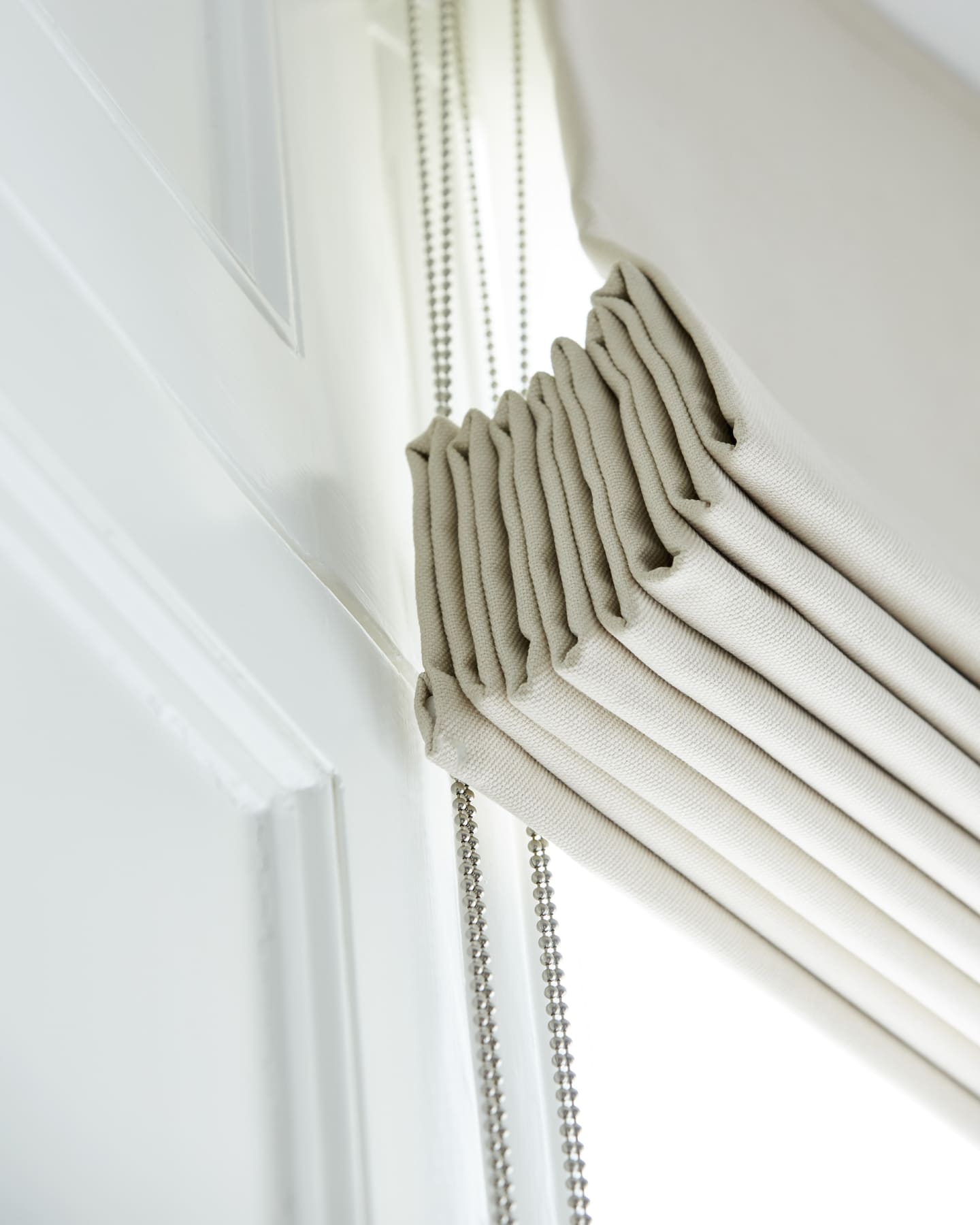 Close up of cream coloured roman blinds