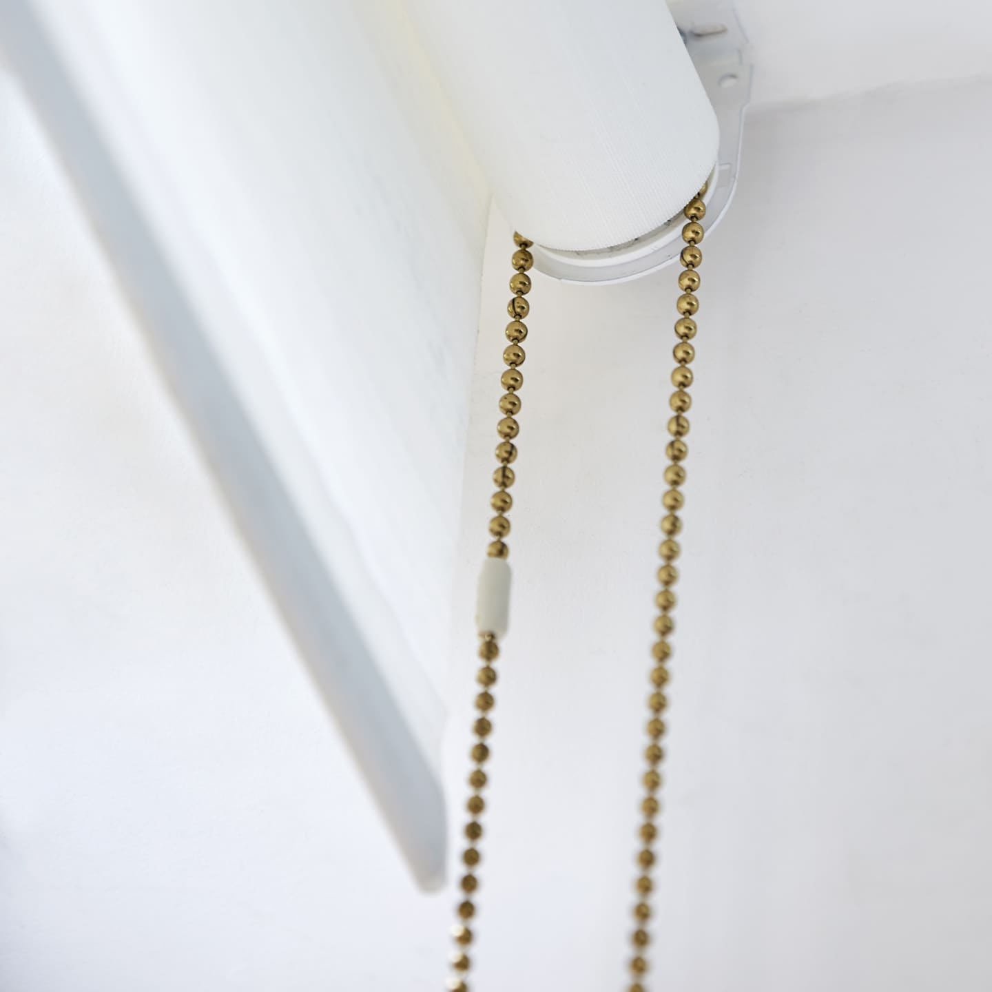 White roller blinds golden chain close up