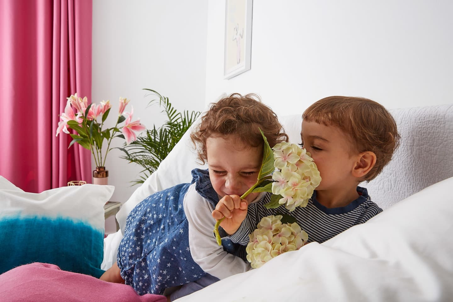 Children holding plants on a bed