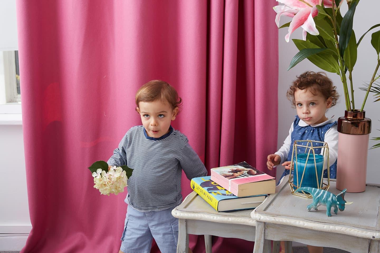 kids play near pink wool curtain
