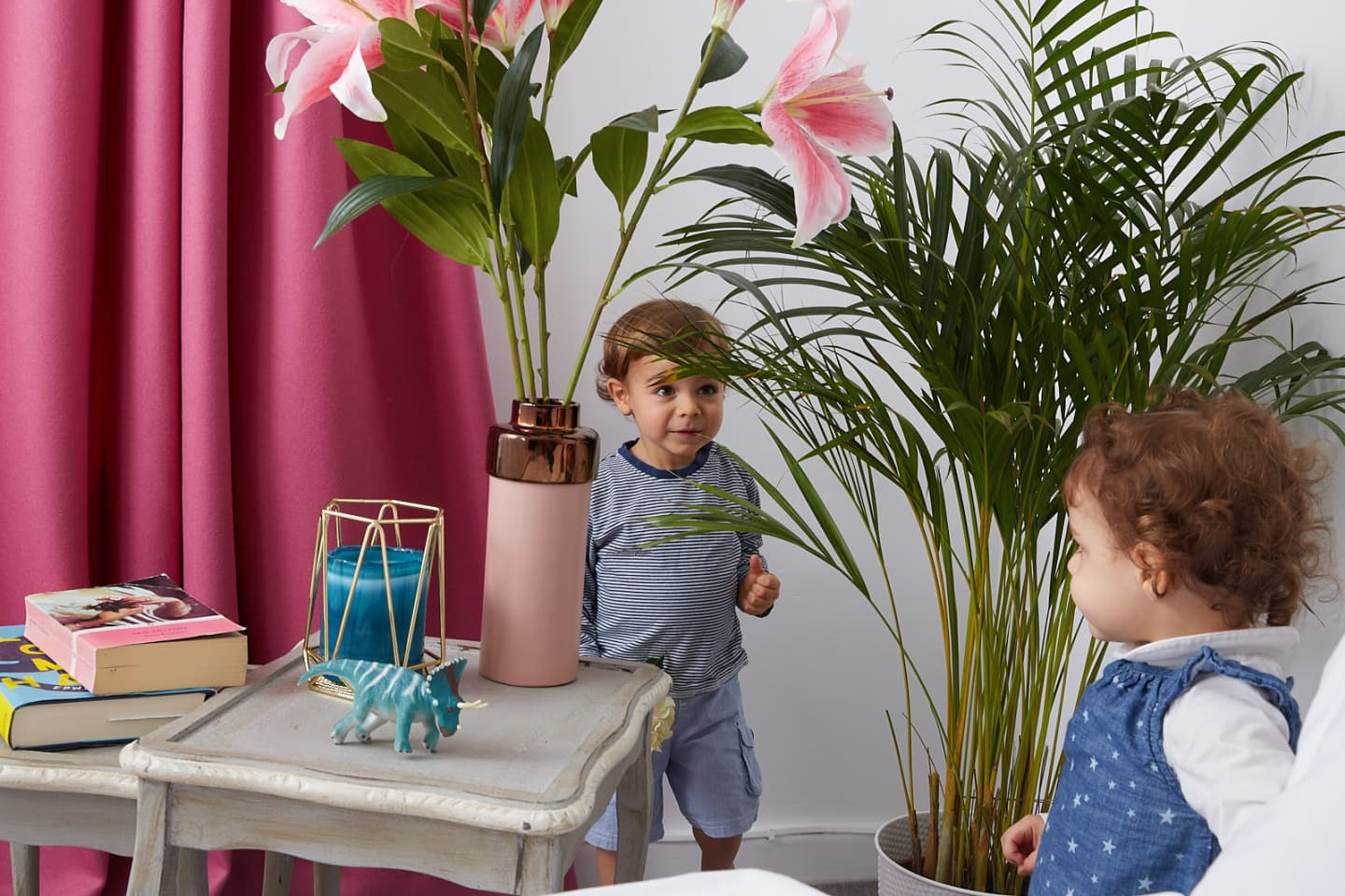 kids playing near plants and pink wool curtains
