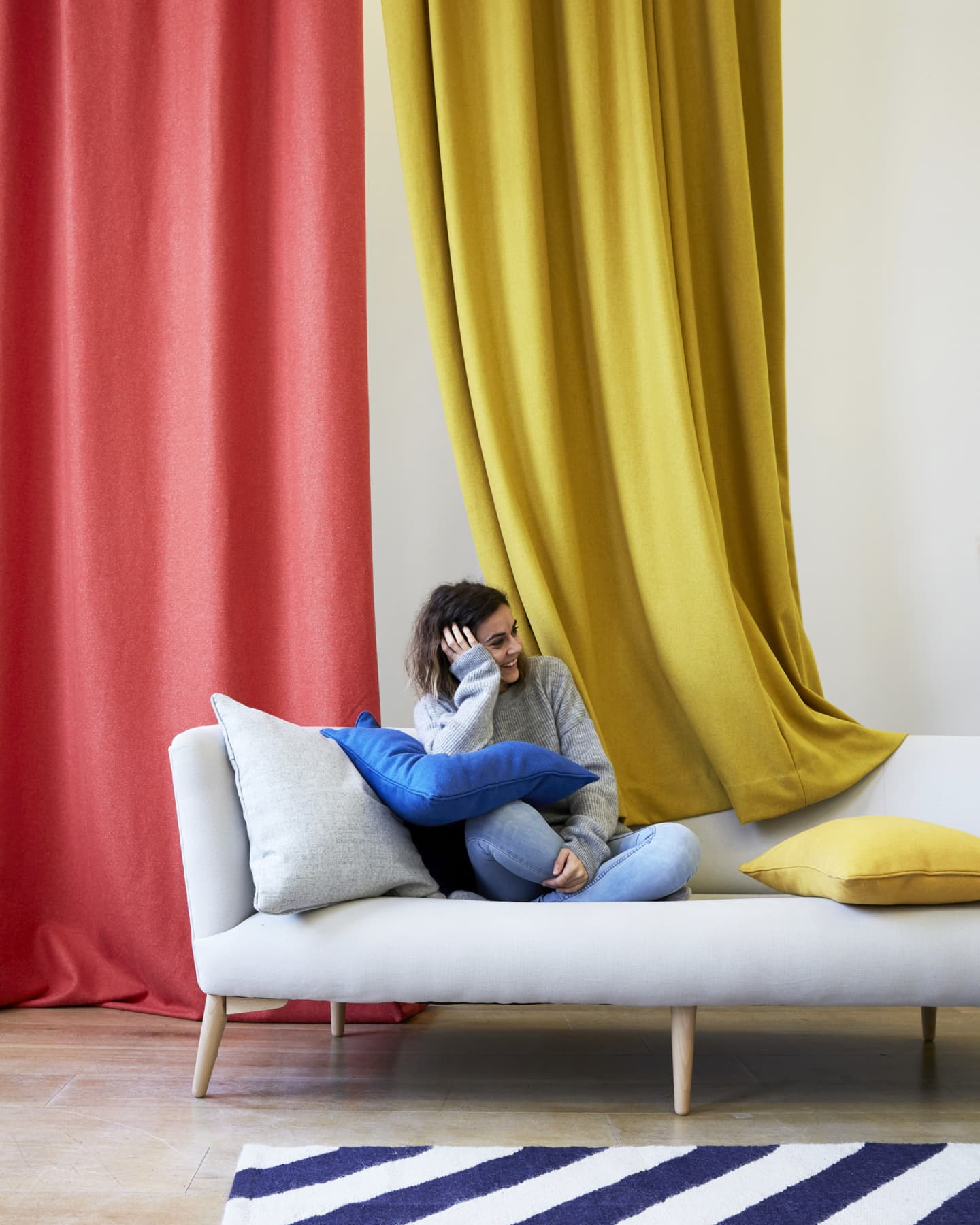 lady on a sofa in front of Red and yellow curtains