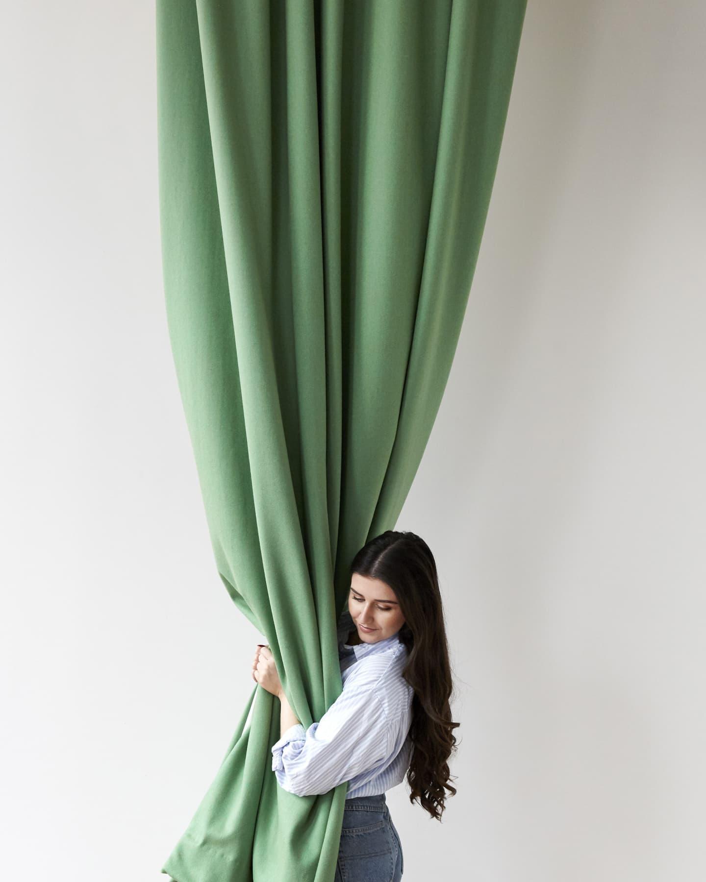 girl hugging a green curtain