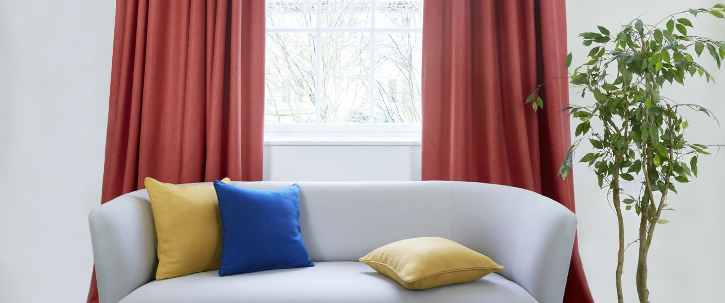 simple sofa with blue and yellow cushions and red curtains