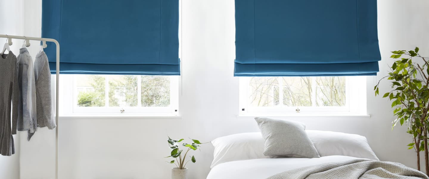 Light blue blackout roman blinds in a white room