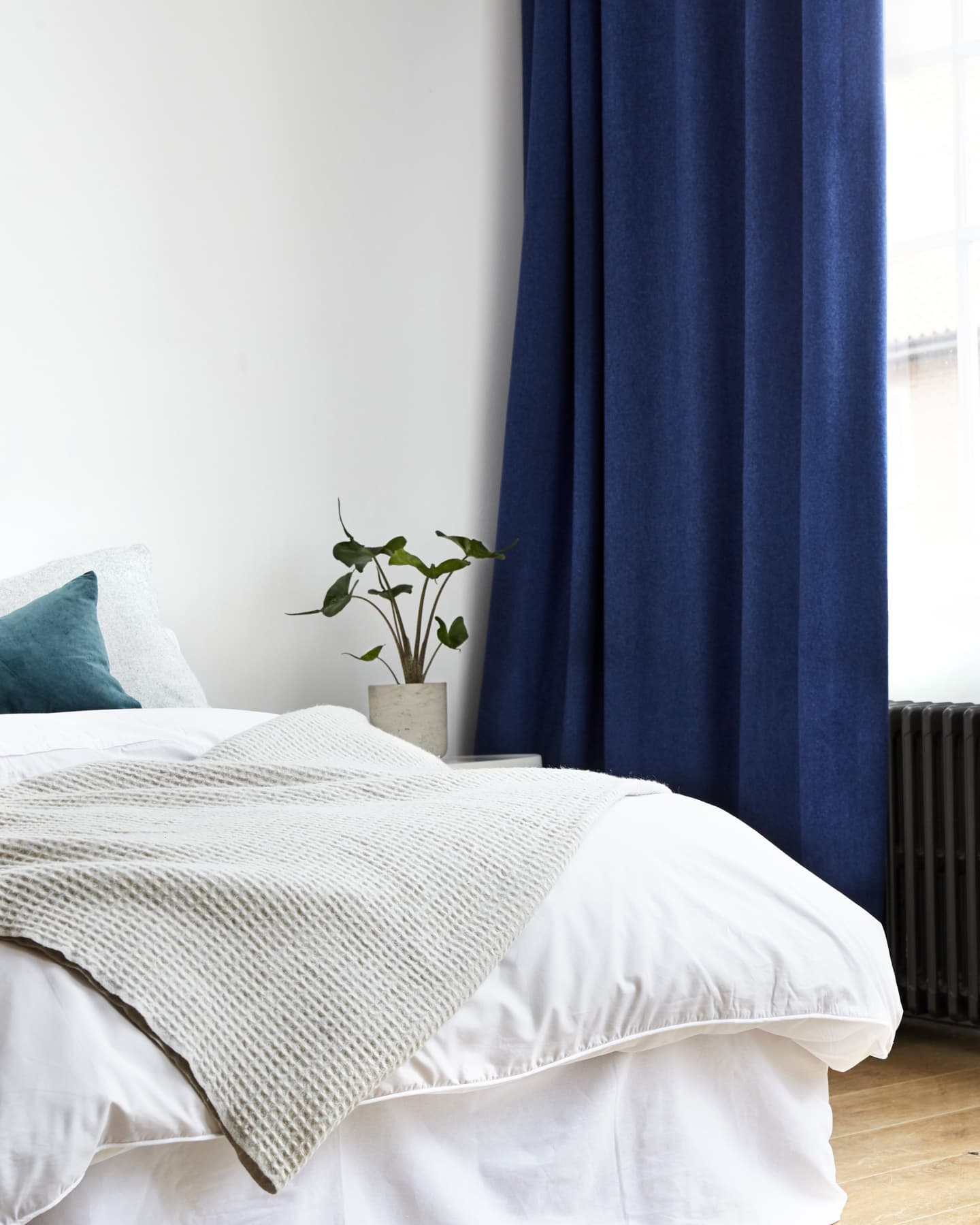 pristine bedroom with white walls and dark curtains