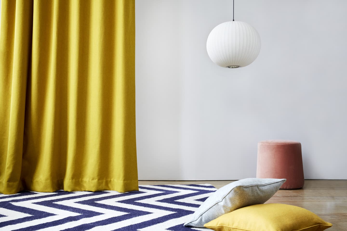 Yellow curtains and cushions on a patterned rug