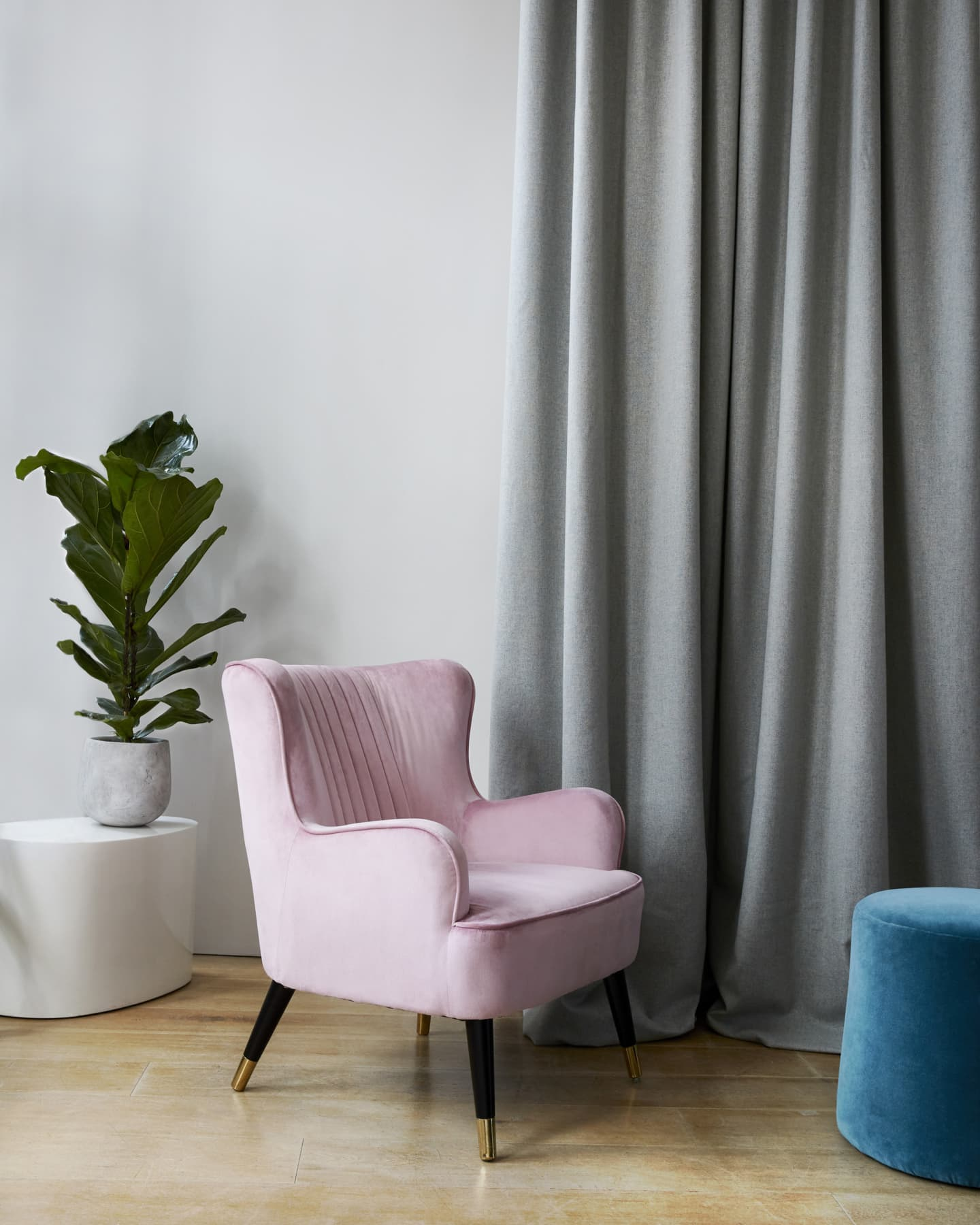 pink chair and plant in front of grey curtain